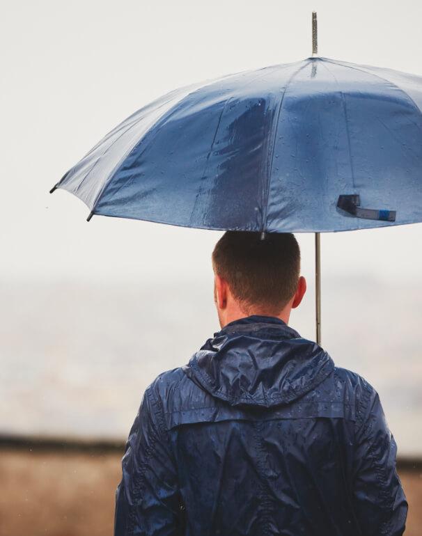 Man walks in a rainstorm with umbrella