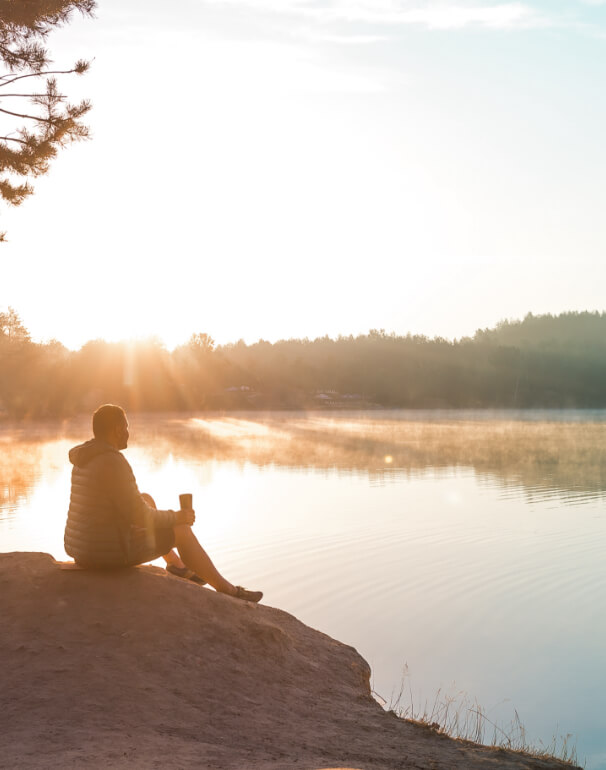 Man enjoys the sunrise and coffee by lake.