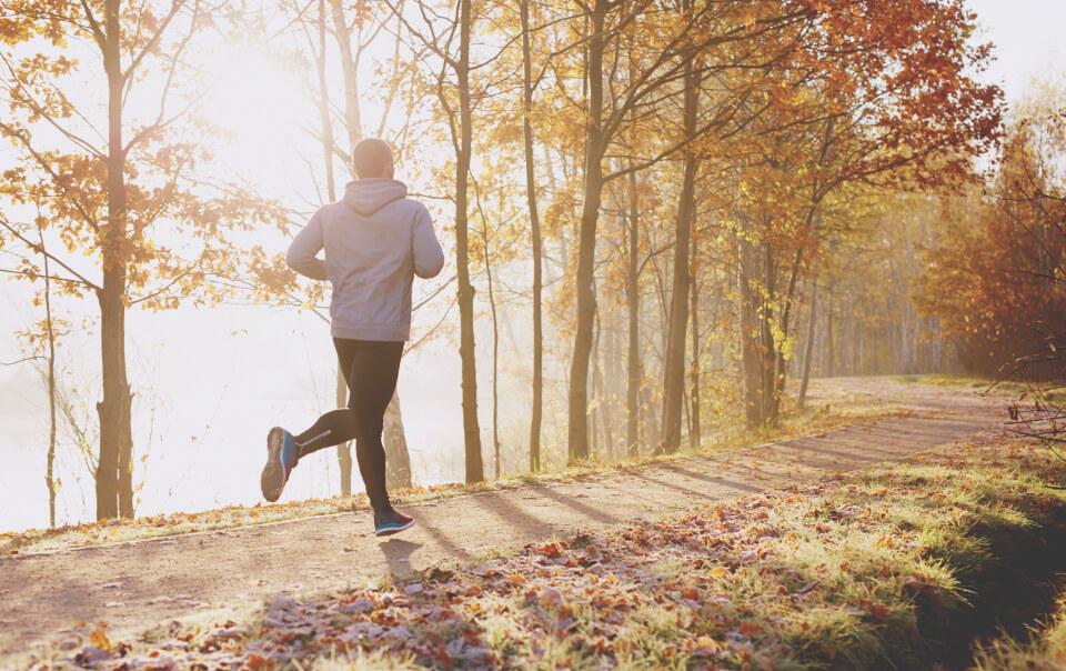 Man runs peacefully on trail at sunrise.